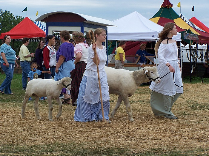 girls leading sheep through faire