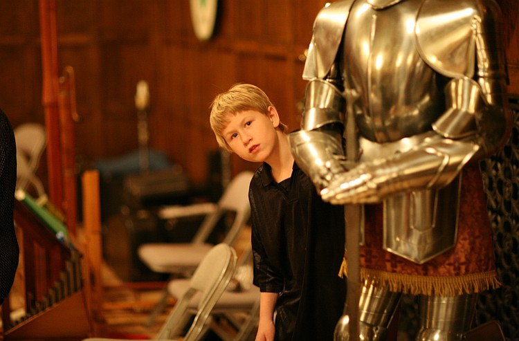 Child looks out from behind a suit of armor