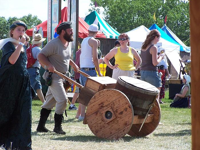 Man pushing a large old wheelbarrow
