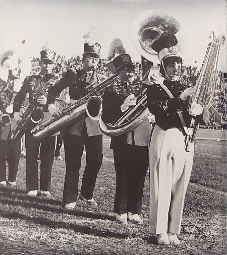 A few members of the band, including a female player, on the field